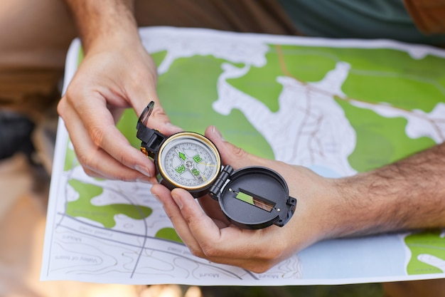Zamknij się z nierozpoznawalnym człowiekiem trzymającym kompas nad mapą, szukając trasy podczas wędrówki, kopiuj przestrzeń