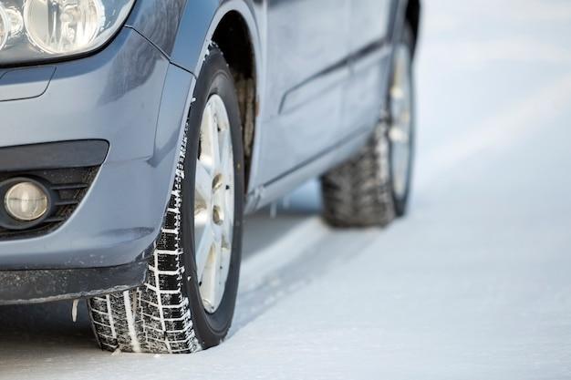 Zamknij się z opon samochodowych zaparkowanych na zaśnieżonej drodze w zimowy dzień. koncepcja transportu i bezpieczeństwa.