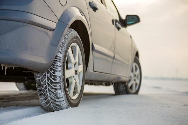 Zamknij się z opony samochodowej zaparkowanej na zaśnieżonej drodze w zimowy dzień. koncepcja transportu i bezpieczeństwa.