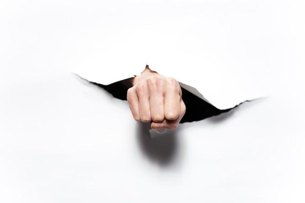 Zamknij się z pięścią przez ciemny otwór białego papieru