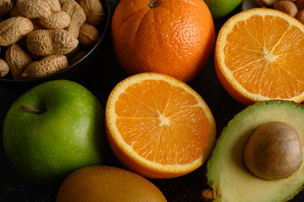 Zamknij się z plasterkiem świeżego pomarańczowego jabłka, kiwi, orzeszków ziemnych i awokado.