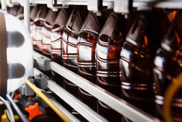 Zamknij się z plastikowych butelek na przenośniku taśmowym. produkcja przemysłowa piwa.