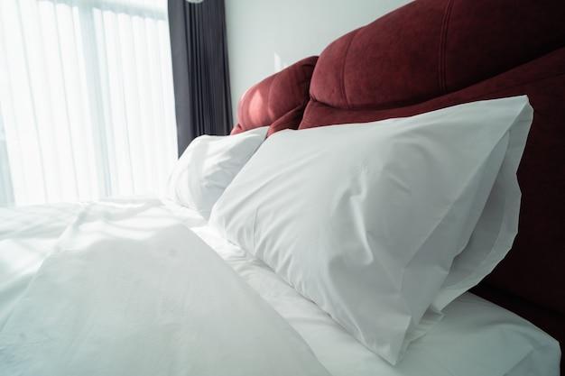 Zamknij się z poduszkami na łóżku w nowoczesnej sypialni