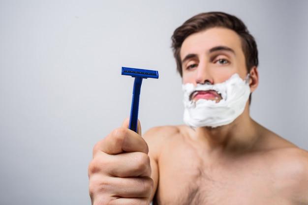Zamknij się z poważnym i skoncentrowanym facetem, który stoi w białym pokoju i pokazuje dobrą brzytwę, którą ma. położył trochę piany na brodzie, a mężczyzna jest gotowy, aby dać jej się porwać. wytnij widok.