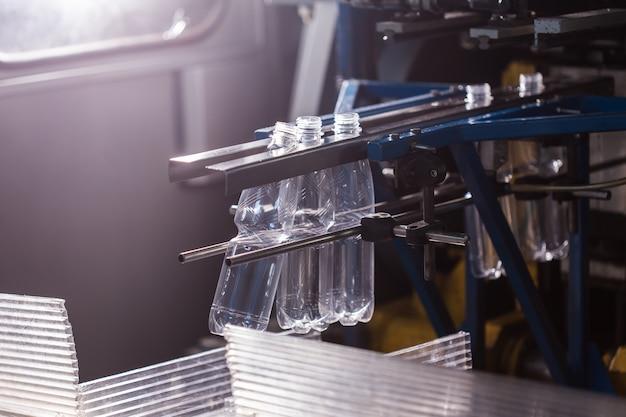 Zamknij się z przemysłu butelkowego. zbliżenie na butelkach wody mineralnej w surowym i liniach