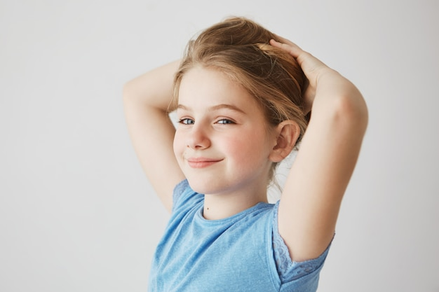Zamknij się z radosna dziewczynka w niebieskim t-shirt patrząc, jasno uśmiechając się i trzymając blond długie włosy rękami. skopiuj miejsce