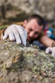 Zamknij się z rąk mężczyzny w proszku magnezowym kredą na skale. ekstremalne wspinanie się po skale po linie z najlepszym ubezpieczeniem