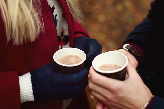 Zamknij się z rąk trzymając papierowe kubki kawy