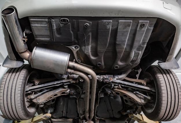 Zamknij się z rury układu wydechowego samochodu w garażu, serwis samochodowy