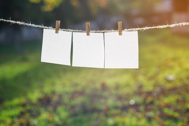 Zamknij się z trzech białych kartek papieru zawieszonych przez drewniane kołki