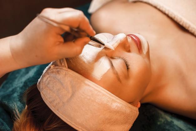 Zamknij się z uroczą kobietą, opierając się na łóżku spa z zamkniętymi oczami, robi białą maskę oczyszczającą skórę.