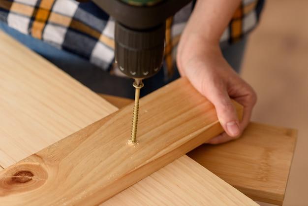 Zamknij się z wiertarką, wiercenie śruby w kawałku drewna, na drewnianej ławce. kobieta pracująca na drewnianej ławce. pasjonat majsterkowania.