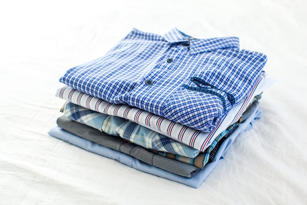 Zamknij się z wyprasowanych i złożonych koszul na stole w domu
