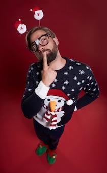 Zamknij się z zamyślony mężczyzna ubrany w ubrania świąteczne