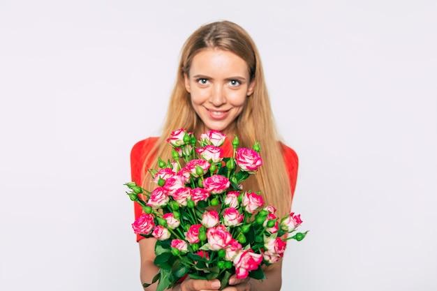 Zamknij się zdjęcie atrakcyjnej kobiety blondynka z dużym bukietem róż na białym tle. koncepcja święta i prezenty. dzień kobiet