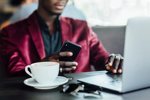 Zamknij się zdjęcie. biznesmen ręcznie za pomocą laptopa i telefonu komórkowego działa online w kawiarni w świetle poranka.