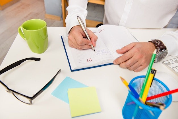 Zamknij się zdjęcie biznesmena sporządzania notatek w swoim notatniku
