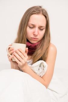 Zamknij się zdjęcie chorej dziewczyny trzymającej kubek gorącej herbaty