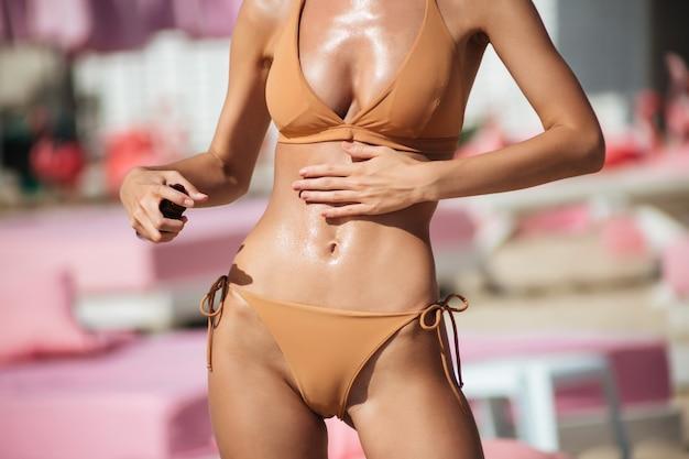 Zamknij się zdjęcie ciała kobiety w bikini na plaży. zdjęcie młodej pięknej kobiety ciała w beżowym stroju kąpielowym za pomocą olejku do ciała na plaży