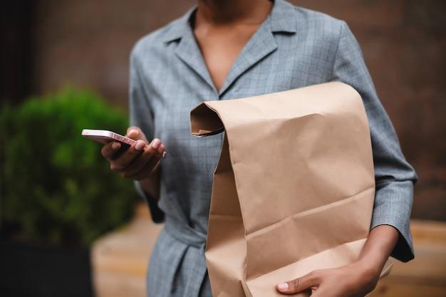 Zamknij się zdjęcie ciała kobiety w szarej sukience stojącej i trzymając papierową torbę