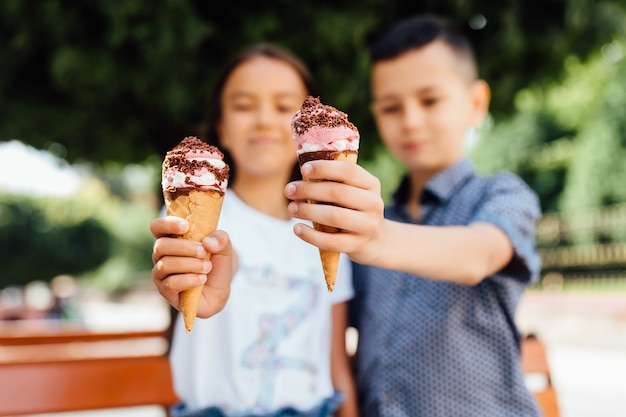Zamknij się zdjęcie. dzieci, brat i siostra na ławce jedzą lody.