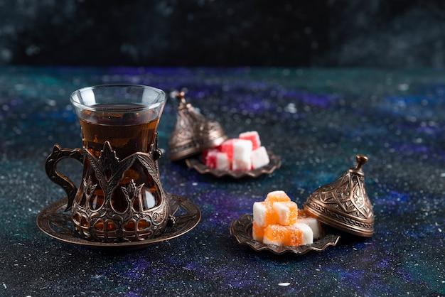 Zamknij się zdjęcie gorącej herbaty i marmolady na niebieskiej powierzchni