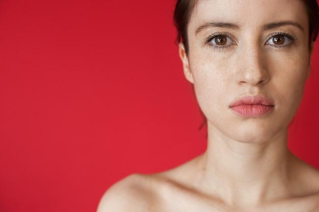 Zamknij się zdjęcie kaukaskiej kobiety z piegami patrząc na kamery, pozując na czerwonej ścianie z wolną przestrzenią z odkrytymi ramionami