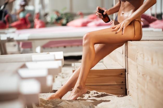 Zamknij się zdjęcie ładnej kobiety nogi w bikini i ręka trzyma butelkę olejku do opalania na plaży. zdjęcie młodej kobiety długie nogi na plaży