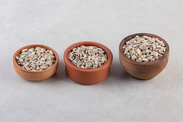 Zamknij się zdjęcie łuskanych nasion słonecznika w miskach.