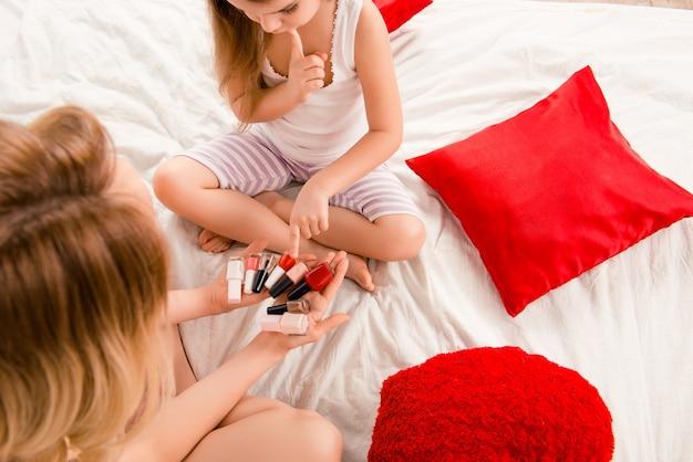 Zamknij się zdjęcie małej dziewczynki wybierając lakier do manicure