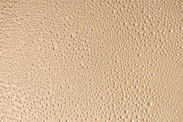 Zamknij się zdjęcie małych kropli wody z konturowym cieniem na białym tle na beżowym kolorze