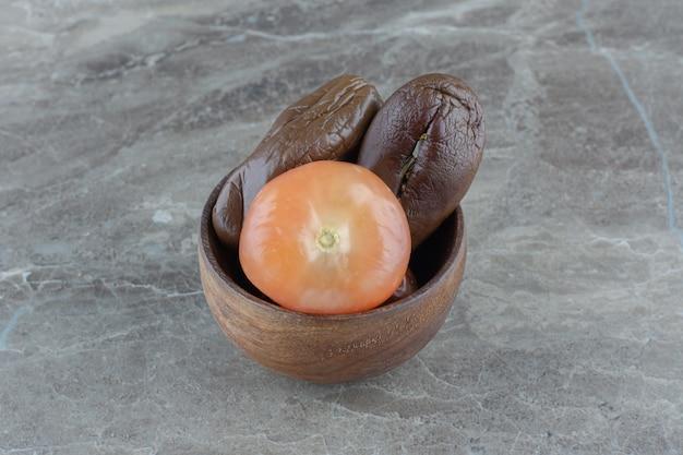Zamknij się zdjęcie marynowanych pomidorów i bakłażanów w drewnianej misce.