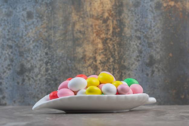 Zamknij się zdjęcie okrągłych kolorowych cukierków na białym talerzu.