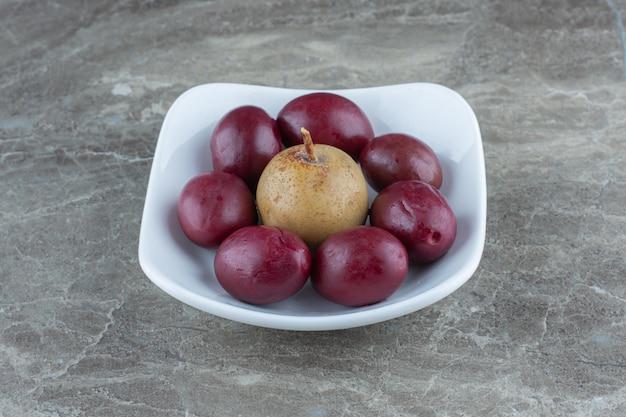 Zamknij się zdjęcie palm z jabłkiem w misce.