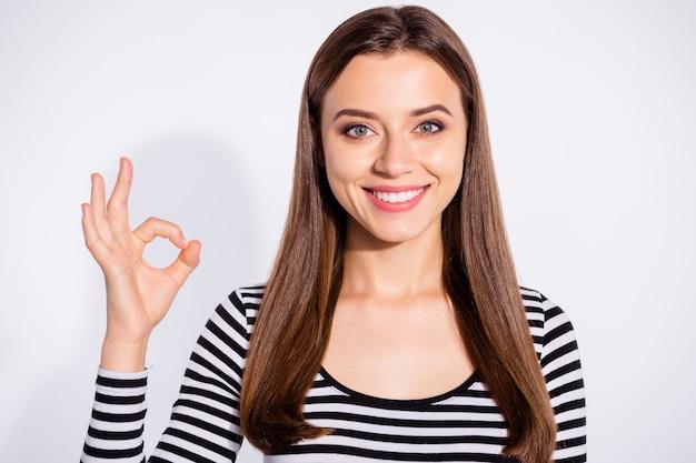 Zamknij się zdjęcie pięknej kobiety co znak w porządku patrząc z uśmiechem toothy noszenie sweter w paski na białym tle nad białą ścianą