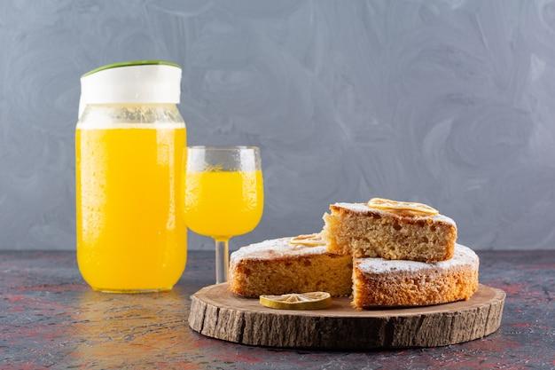 Zamknij się zdjęcie plasterków ciasta i świeżego soku w stylu rustykalnym.