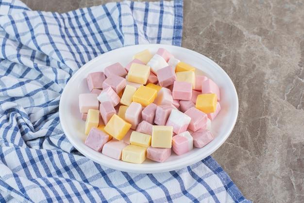 Zamknij się zdjęcie pyszne słodkie cukierki na białym talerzu.
