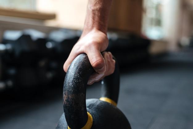 Zamknij się zdjęcie ręki fitness i kettlebell. bokiem