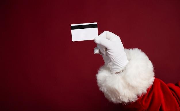 Zamknij się zdjęcie ręki świętego mikołaja w białej rękawiczce z karty kredytowej