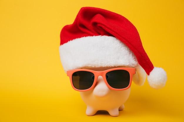 Zamknij się zdjęcie różowej skarbonki z okulary przeciwsłoneczne boże narodzenie kapelusz na białym tle na żółtym tle ściany. koncepcja bogactwa usług bankowości inwestycyjnej akumulacji pieniędzy. skopiuj makiety reklamowe.