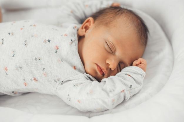Zamknij się zdjęcie śpiącego dziecka w ciepłych ubraniach z czarnymi włosami, które czują się bezpiecznie we własnym łóżku
