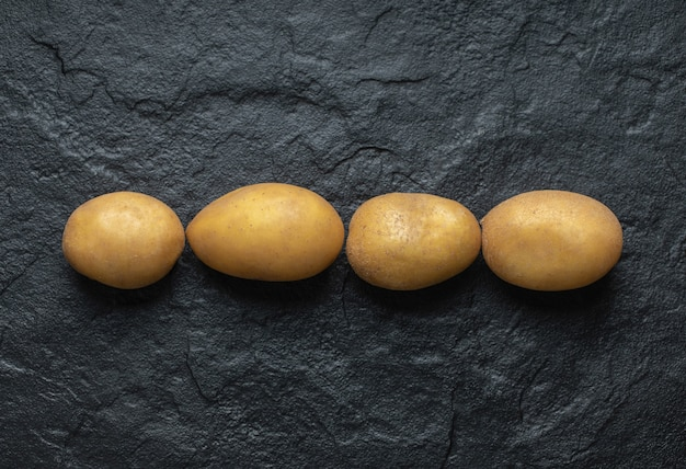 Zamknij się zdjęcie stosu świeżych ziemniaków organicznych na czarnym tle.