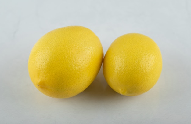 Zamknij się zdjęcie świeże, dojrzałe cytryny na białym tle.