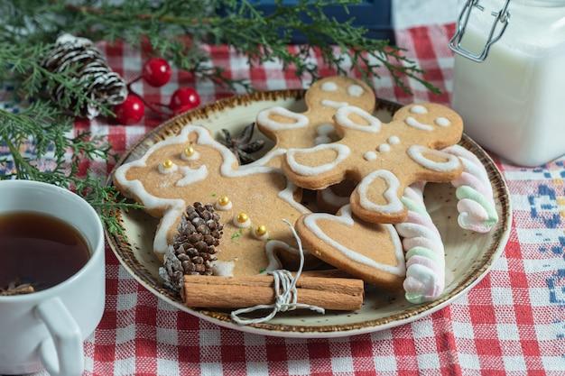 Zamknij się zdjęcie świeżej herbaty i świąteczne ciasteczka.