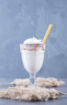 Zamknij się zdjęcie świeżo przygotowanego mleka wstrząsnąć na szarym tle.