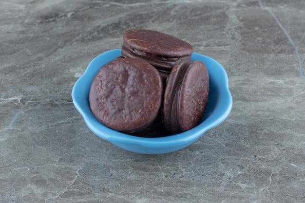 Zamknij się zdjęcie świeżych domowych ciasteczek czekoladowych na niebieskim misce.
