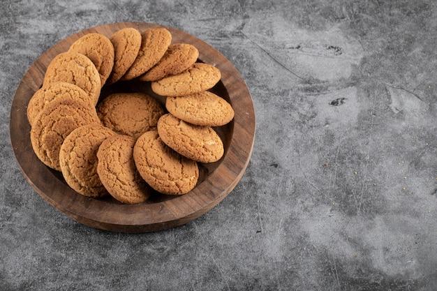 Zamknij się zdjęcie świeżych domowych ciasteczek. pyszne ciasteczka na drewnianej tacy.