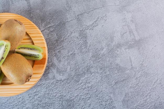 Zamknij się zdjęcie świeżych organicznych kiwi na drewnianym talerzu.