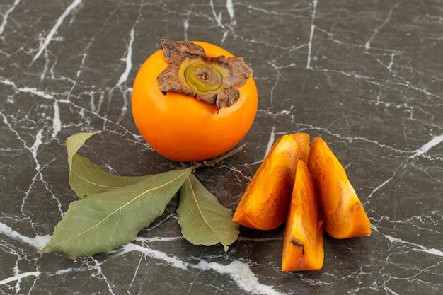 Zamknij się zdjęcie świeżych organicznych persimmons. w całości lub w plasterkach.
