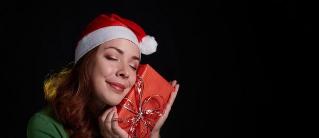 Zamknij się zdjęcie szczęśliwej kobiety w boże narodzenie kapelusz z prezentem w jej ręce na czarnym tle. baner z miejscem na kopię